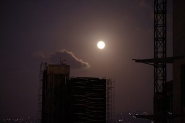 Close up to the full moon showing a silhouette of a building under construction