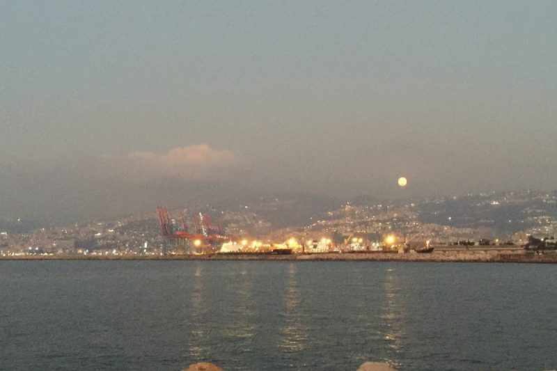 Large orange tinted Harvest Moon appearing over Beirut at sunset time